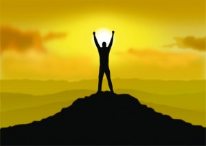Man on top of a mountain with arms raised at sunset